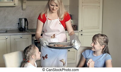 Tea Time - Mother of two girls putting the tray with...