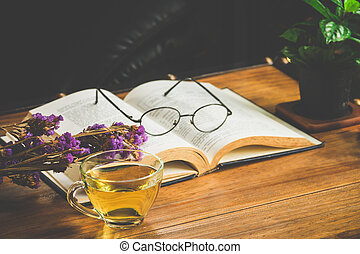 Tea time with reading book on table in cafe