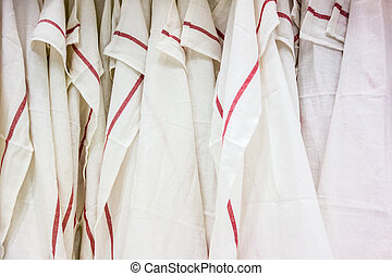 a lot of white tea towel with a red stripe hangen on the wall