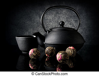 Tea utensil and buds on a black background