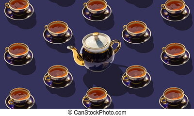 Many cups of tea and one teapot in the center. Ceramic tableware  revolve around their axes. Stop motion animation.  Flat lay, top view. Diagonal isometric view. Seamless loop video.