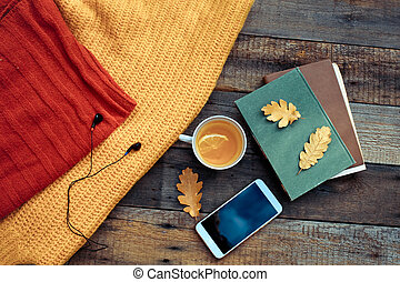 Tea with a lemon and autumn leaves on vintage wood background - seasonal relax concept