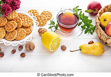 Tea with herbs fruits and cookies. Still