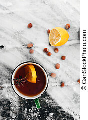 tea with lemon and cardamom on a snowy background in the forest top view
