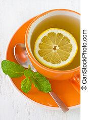 tea with lemon in orange cup
