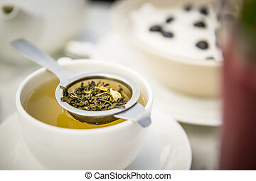 Tea with teacup and tea strainer