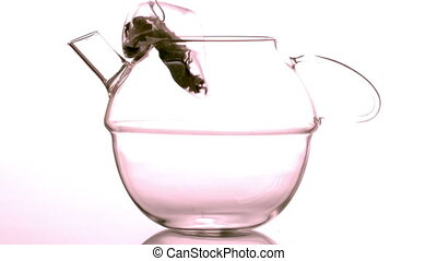 Teabag falling into glass teapot in slow motion