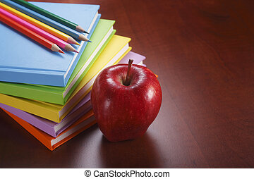Teacher - A stack of books with some pencils and an apple.