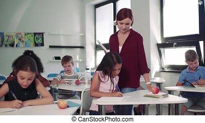 Teacher among small school children on the lesson, ...