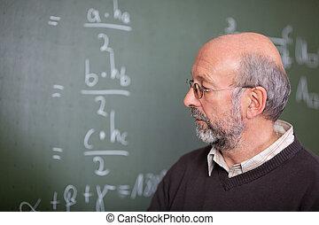 Teacher and blackboard - Portrait of teacher standing in ...