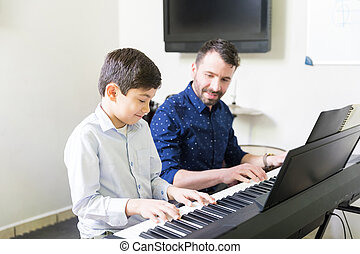 Teacher And Boy Playing Electric Piano In Music Session