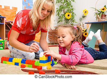 Teacher and child are playing with bricks - Teacher and...