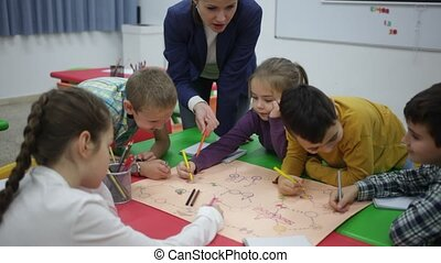 Pretty boys and girls with teacher draw a table game in classroom