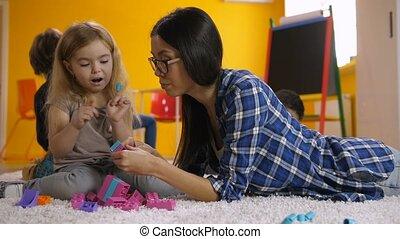 Teacher and cute girl communicating in kindergarten