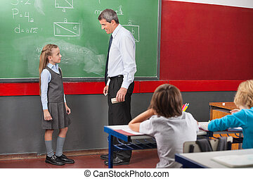 Teacher And Girl Discussing Lesson In Classroom
