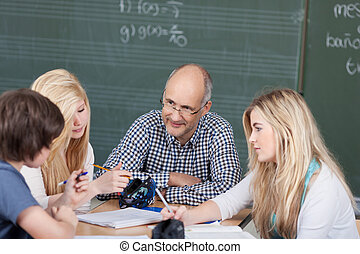 Teacher and his students in a group discussion seated around...