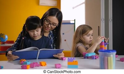 Teacher and kid reading book in kindergarten
