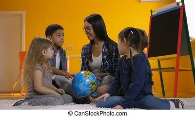 Teacher and kids discussing globe in kindergarten - Positive...