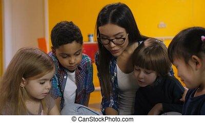 Teacher and kids learning in preschool class - Portrait of...