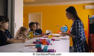 Teacher and kids making origami ship in art class