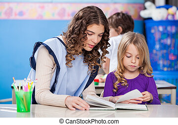 Teacher And Little Girl Reading Book In Classroom
