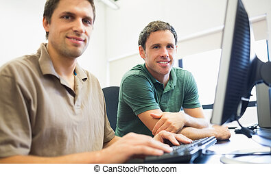 Teacher and mature student in computer room