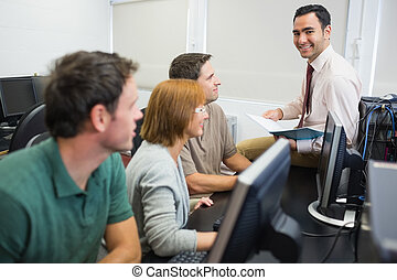 Teacher and mature students in computer room