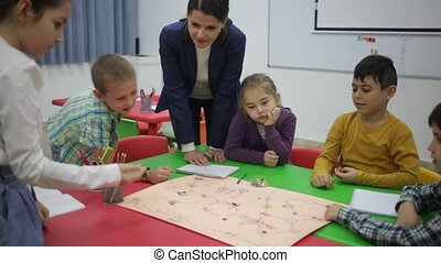 Teacher and happy children sitting at table with board game and dice in school