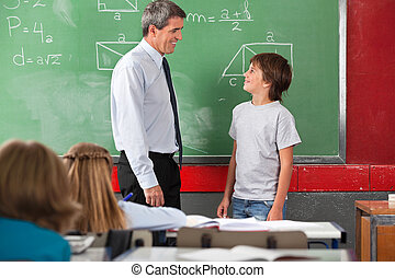 Teacher And Schoolboy Looking At Each Other In Classroom -...