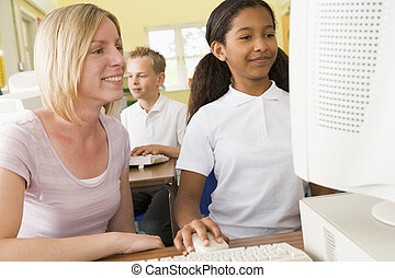 Teacher and schoolgirl studying in front of a school computer
