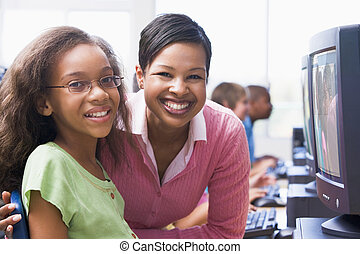 Teacher and student at computer terminal with students in...