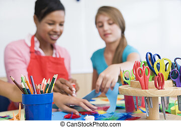 Teacher and student in art class with supplies in foreground (selective focus)
