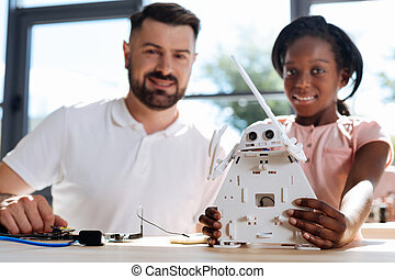 Teacher and student posing with a new robot