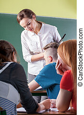 Teacher and students during classes - Female teacher and...