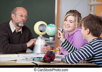 Teacher And Students Looking At Planetarium Model At Desk