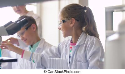 teacher and students studying chemistry at school -...