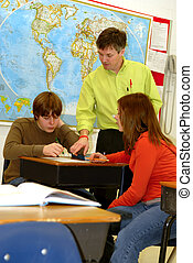 A teacher goes over lessons with teenage students in classroom setting.