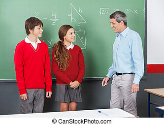 Teacher And Teenage Students Looking At Each Other