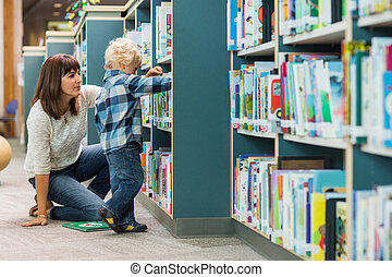 Teacher Assisting Boy In Selecting Book From Bookshelf