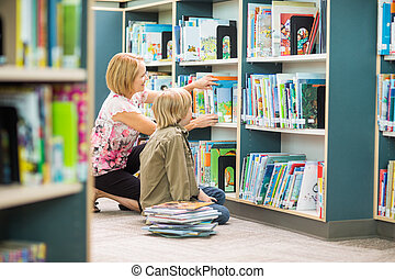 Teacher Assisting Boy In Selecting Books In Library - Mature...