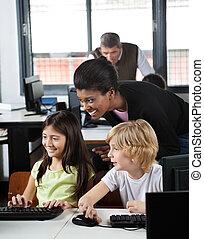Young female teacher assisting schoolchildren in using desktop PC at computer lab