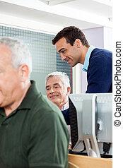 Teacher Assisting Senior Man In Computer Class