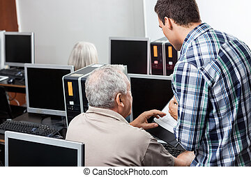 Teacher Assisting Senior Man In Using Computer At Classroom