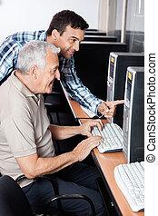 Teacher Assisting Senior Man In Using Computer