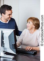 Teacher Assisting Senior Student In Computer Class