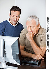 Teacher Assisting Senior Student In Computer Class