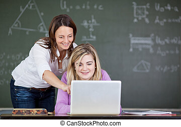 Teacher Assisting Student In Using Laptop At Desk
