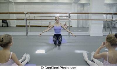 Teacher at children's ballet shows girls exercises for toe of foot.