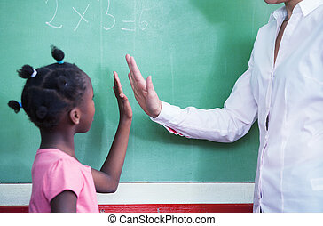 Teacher congratulating with afro american female student in ...