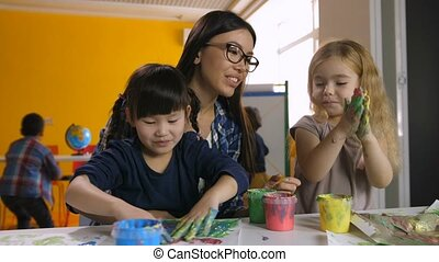 Teacher developing creativity of kids at art class